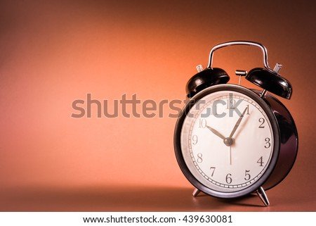 Black classic style alarm clock on red background with vintage tone colour, Clock concept, Retro clock at Ten o'Clock and Five minute. - stock photo