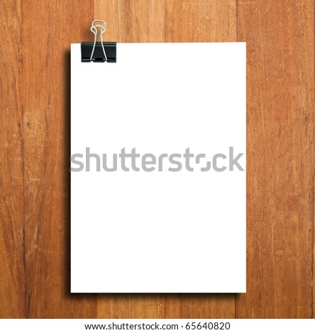 Black clip and White blank note paper hang on wood pane - stock photo