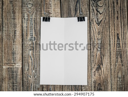 Black clip and White paper hang on wood background - stock photo