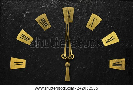 Black clock with golden arms indicating it's about time. - stock photo