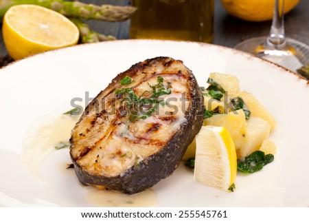 Black cod steak with potatoes - stock photo