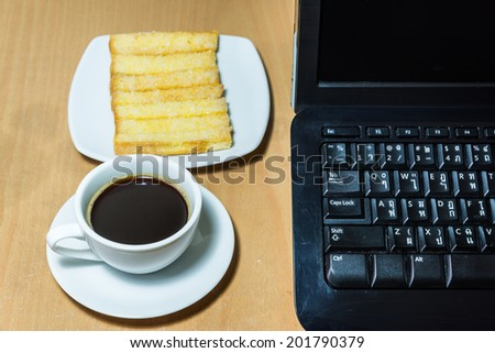 black coffee and baked bread on a table with old computer - stock photo