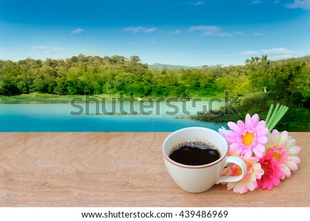 black coffee and bunch of flower with lake and mountain background - stock photo