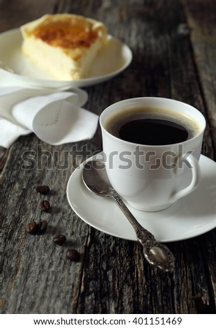 Black coffee and cheesecake and coffee beans