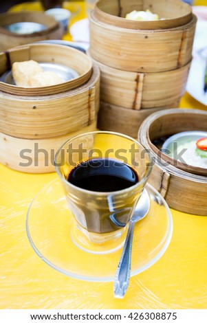Black coffee and dim sum on the yellow table - stock photo