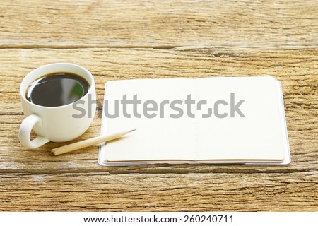 Black coffee and notebook on wooden table