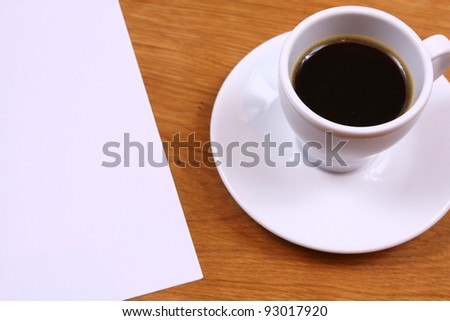 Black coffee and paper on desk