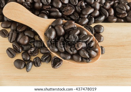 black coffee bean in wooden spoon on wooden background - stock photo