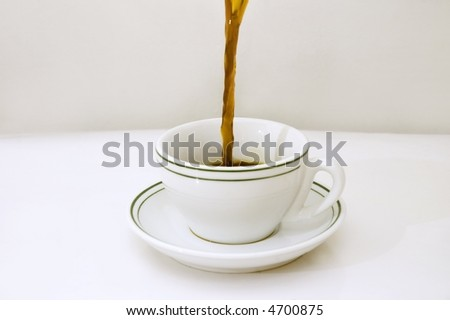 Black coffee being poured on a white cup over white background - stock photo
