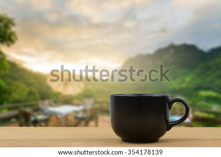 black coffee cup on wooden table over blurred image of beautiful dinner place and nice view over the mountain, Chiang Mai, Thailand - stock photo