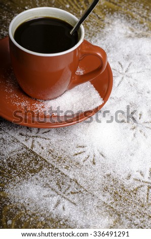 Black coffee in a red cup on a wooden background.