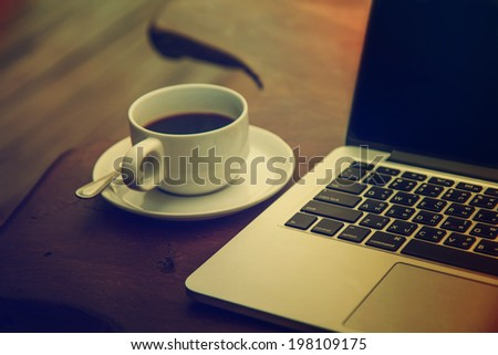 Black coffee in a white cup on a table with a computer. - stock photo