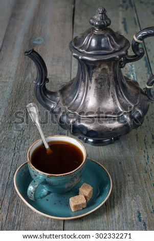 Black coffee in blue vintage cup and antique silver coffee pot on a old dark wooden boards - stock photo