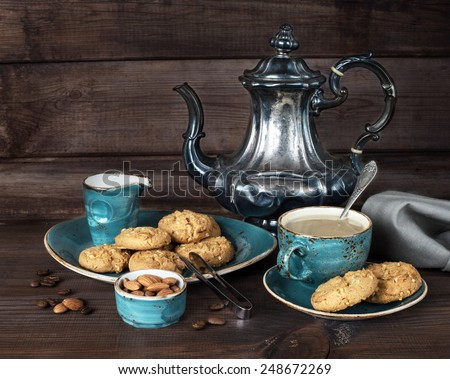 Black coffee in blue vintage cup, cookies and antique silver coffee pot on a old dark wooden boards - stock photo