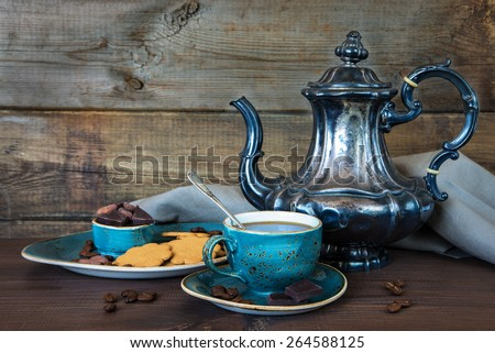 Black coffee in blue vintage cup, cookies, chocolate and antique silver coffee pot on a old dark wooden boards - stock photo