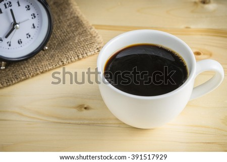 Black coffee in cup of coffee on wooden background - stock photo