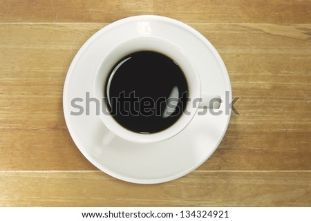 Black coffee in white cup on old wood desk.