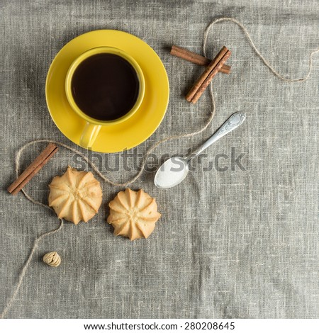 Black coffee in yellow cup with cookies and cinnamon sticks on grey fabric background - stock photo