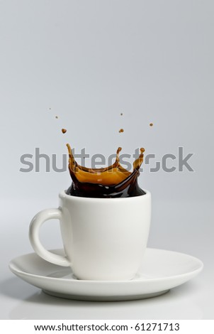 Black coffee splashing in white cup on white background.