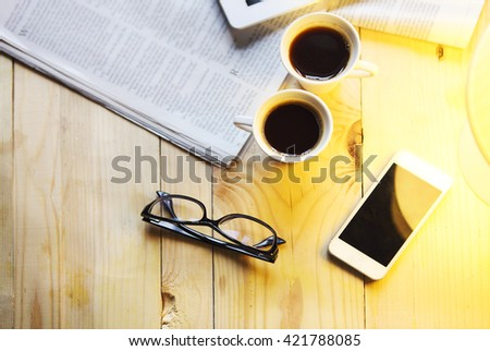 Black coffee with blank digital tablet and mobile phone, magazines and glasses on the table. Break concept - stock photo