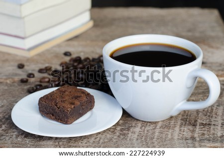 Black coffee with chocolate brownie  on grained wood