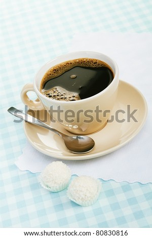 black coffee with coconut candies on a blue tablecloth - stock photo