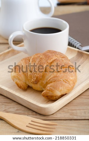 Black coffee with croissants on the wooden tray