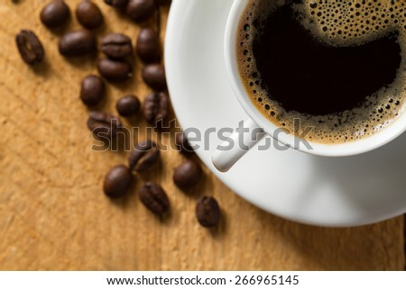 Black coffee with froth on wooden table (top view) - stock photo