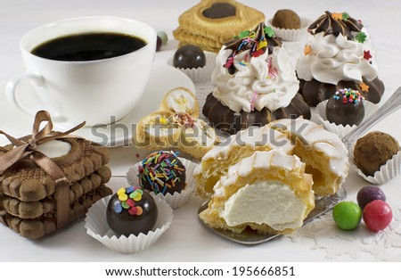 Black coffee with sweet baked things, candies and cupcakes - stock photo