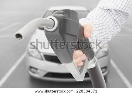 Black color fuel pump gun in hand with car on background - stock photo
