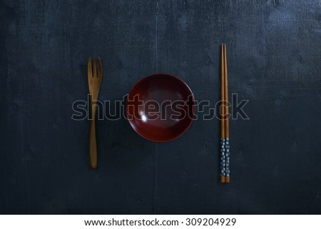 Black color wooden table top view. On the table are the Japanese wooden spoon, chopsticks, bowl . - stock photo