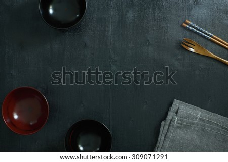 Black color wooden table top view. On the table are the Japanese wooden spoon, chopsticks, bowl and table linen. - stock photo