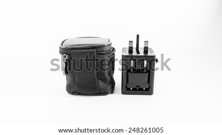 Black colour universal power plug adapter with dual usb port in a pouch for traveller in UK, Europe and USA or Australia. Isolated on white background. - stock photo