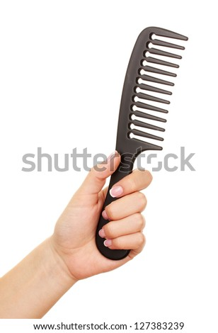 Black comb in female hand isolated on white