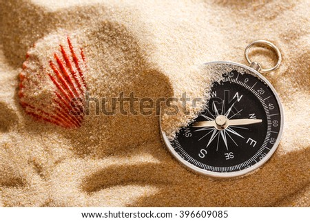 Black compass and sea shell in sand closeup - stock photo