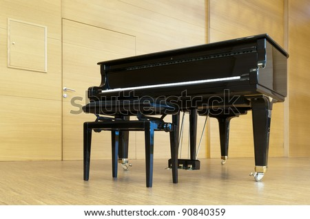 black concert piano is standing on a wooden stage with stool ready for playing - stock photo