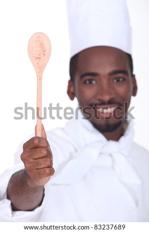 black cook showing a wooden spoon - stock photo