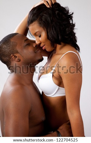 Black couple in romantic foreplay, she is wearing only bra and panties and sitting in his lap while he kisses her affectionately