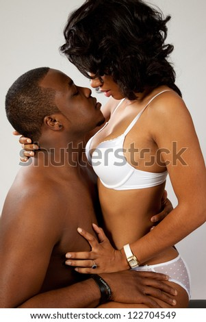 Black couple in romantic foreplay, she is wearing only bra and panties and sitting in his lap while he kisses her affectionately - stock photo