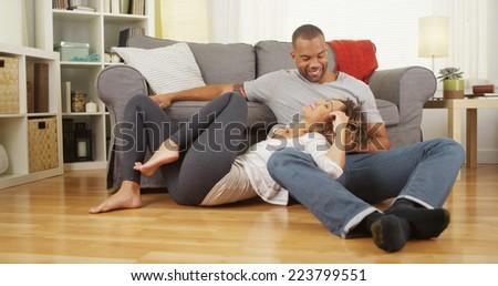 Black couple sitting on floor talking - stock photo