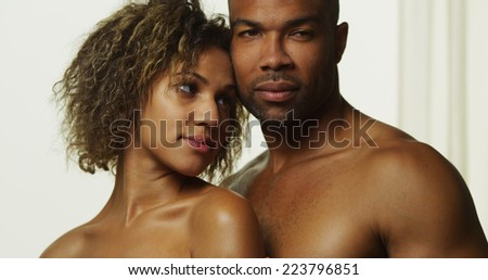 Black couple standing together by window