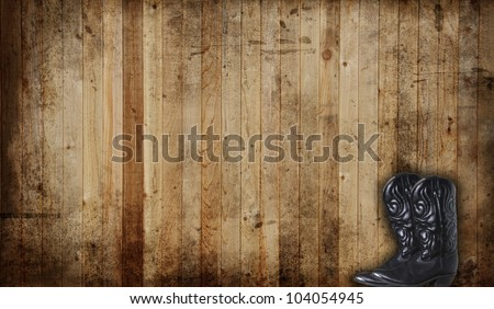 Black Cowboy boots against a weathered cedar background panel. - stock photo