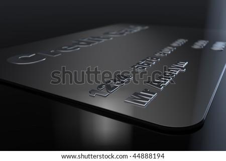 Black credit card lying on black floor - stock photo