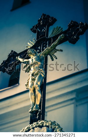 black cross with gold jesus and chapel as background in retro style - stock photo