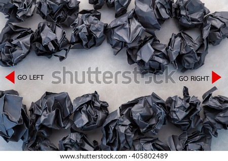 black crumpled paper ball with left right direction on grey leather background business concept.jpg - stock photo