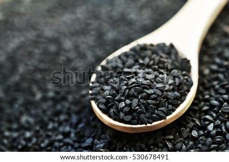 Black cumin (nigella sativa or kalonji) seeds in spoon on wooden background, selective focus, toned
