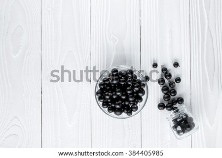 black currant in glassware on white wooden table top view - stock photo