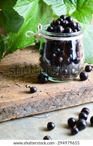 black currant in jar on a wooden tablefresh fruit. Antioxidants - stock photo