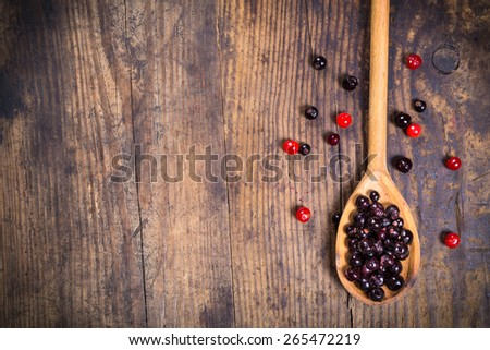 black currant in spoon and viburnum on wooden background with empty copy space - stock photo