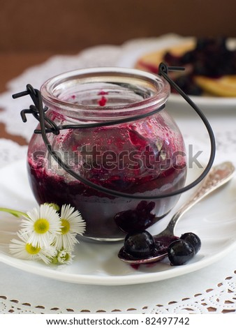 Black currant jam in glass jam-jar. Selective focus - stock photo
